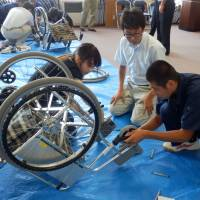 High school students try their hand at restoring a corroded wheelchair destined for Sri Lanka during a seminar held in Daisen, Akita Prefecture, on Aug. 7. | MAGDALENA OSUMI