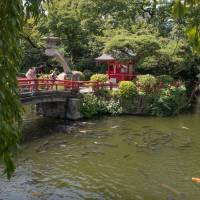 A pond on the shrine's grounds, attracts the attention of a young family. | STEPHEN MANSFIELD