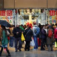 Fast fashion: Shoppers gather outside a Uniqlo store in Tokyo in April. While Uniqlo is currently expanding in China, where its brand is seen as aspirational, market watchers believe it may be on the decline in Japan. | BLOOMBERG