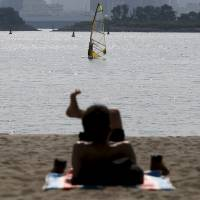 Solar power: A man soaks up some rays on the beach at Odaiba Seaside Park in Tokyo earlier this month. A recent heat wave hasn't led to disastrous power shortages. | REUTERS