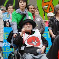 Survivor: A woman who survived the atomic bombing of Hiroshima, but whose father didn't, takes part in a demonstration against nuclear power in New York in April. | KYODO