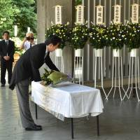 Paying respect: Prime Minister Shinzo Abe leaves a boquet of flowers during a visit to Chidorigafuchi National Cemetery for unknown war victims in Tokyo on Aug. 15. | AFP-JIJI