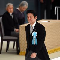 In remembrance: Prime Minister Shinzo Abe (foreground) walks toward an altar past Emperor Akihito (background, left) and Empress Michiko as he prepares to read a statement of condolence at a memorial service for war victims in Tokyo on Aug. 15. | AFP-JIJI