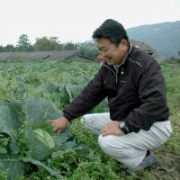 Country boy: A man in a Tokushima Prefecture village checks some crops. A recent TV show called 'Napoleon's Village' focused on depopulation in Japan's rural areas. | KYODO