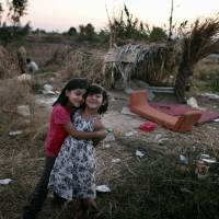 Living in poverty: Migrant children pose in front of makeshift shelters on the Greek Aegean island of Kos on Aug. 16.   AFP-JIJI