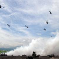 Defenders: Ground Self-Defense Forces helicopters fly over armored vehicles during an annual live-fire exercise at the Higashi-Fuji firing range in Gotenba, Shizuoka Prefecture. | AFP-JIJI