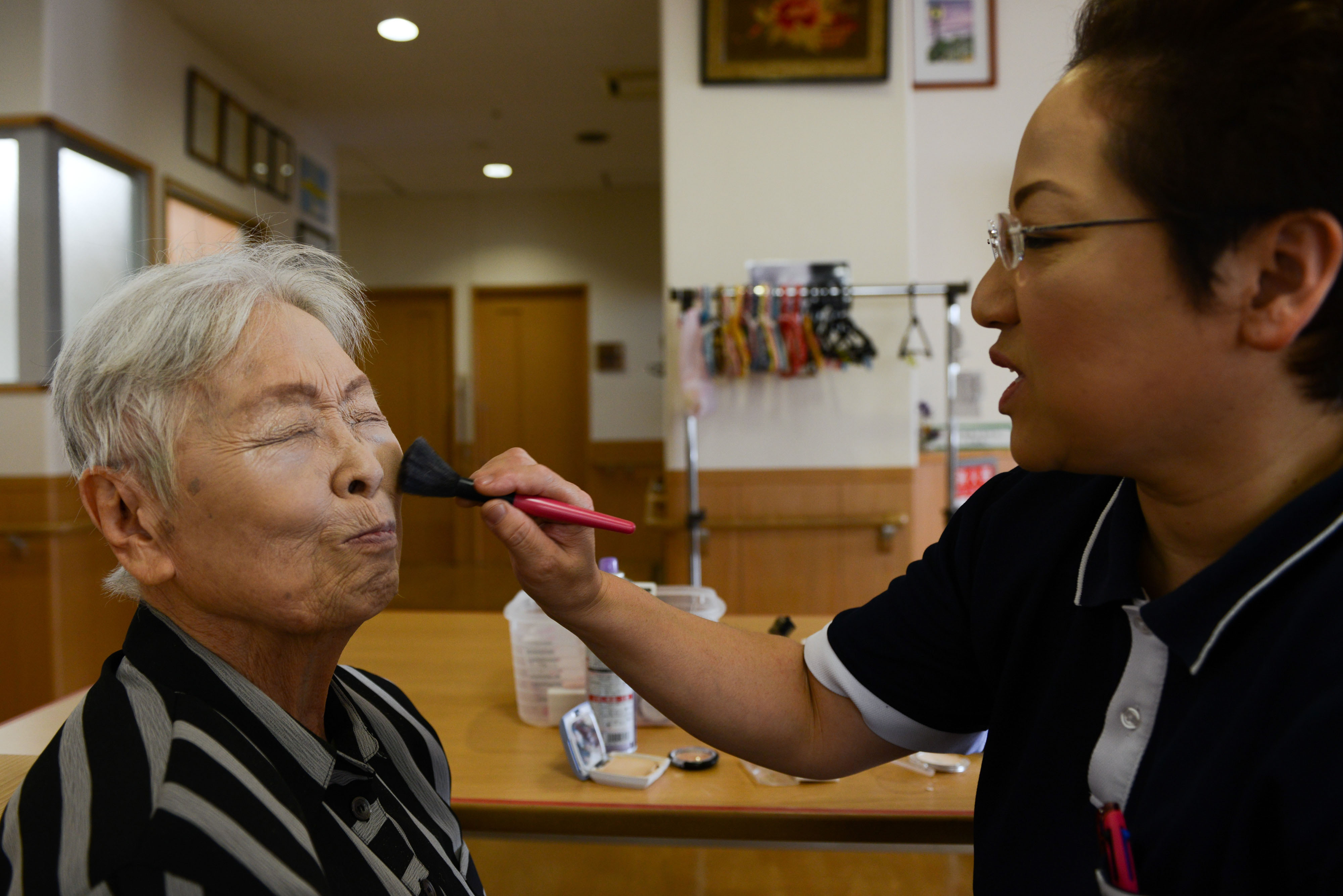 Boom and bust: A worker applies make up to an elderly resident at a care facility in Osaka. Japan is grasping for ways to satisfy the increasing need for such facilities as postwar baby boomers hit old age | NORIKO HAYASHI / BLOOMBERG