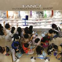 Big spenders: Chinese tourists shop at a cosmetics store in Tokyo's Ginza shopping district in June.   AP