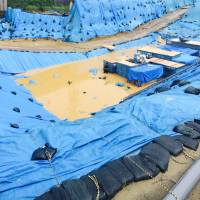 Dirty secret: Japanese workers toil without safety gear at the flooded U.S. military dioxin dump site in Okinawa City on Sunday. The land used to be part of Kadena Air Base, the Pentagon's busiest Okinawa installation during the Vietnam War. | KEN NAKAMURA-HUBER