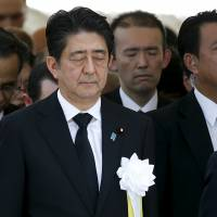 Prime Minister Shinzo Abe offers a silent prayer for victims of the 1945 atomic bombing of Nagasaki during a ceremony Sunday commemorating the 70th anniversary of the bombing of the city. | REUTERS