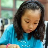 Sawa Kurahashi tries her hand at making a pair of chopsticks during the first week-long summer camp at Moriumius last month. | ROB GILHOOLY