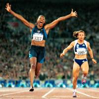 American Marion Jones celebrates as she crosses the finish line to win the 100 meters at the 2000 Summer Olympics. Jones won five medals in Sydney but was stripped of them all for steroid use. | AP