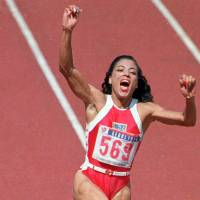 Florence Griffith Joyner celebrates after winning the women's 100-meter final at the 1988 Seoul Olympics, where she claimed three golds and a silver. | AP