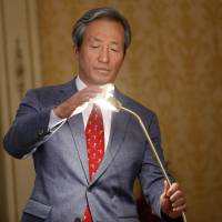 FIFA presidential candidate Chung Mong-joon adjusts a lamp during a press conference in Paris on Monday. | AP