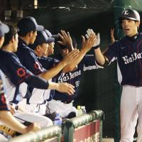 The Lions' Shogo Akiyama is congratulated his teammates after hitting a home run during the ninth inning of Seibu's win over Tohoku Rakuten. | KYODO