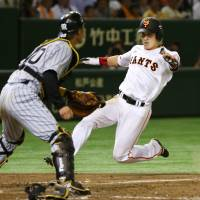 Yasuyuki Kataoka scores on a double by Hayato Sakamoto during the fifth inning of the Giants' 12-3 win over the Tigers on Wednesday at Tokyo Dome.   KYODO