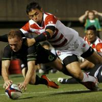 Japan's Ayumu Goromaru, seen tackling the World XV's Andrew Ellis, in last Saturday's test match in Tokyo, and his teammates take on Uruguay on Saturday in Fukuoka. | REUTERS