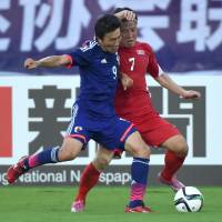 Japan's Kensuke Nagai (left) competes with North Korea's Ri Hyok Chol during their East Asian Cup game in Wuhan, China, on Sunday. | AFP-JIJI