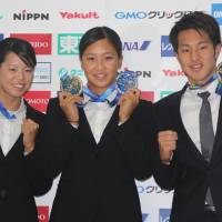 Japan swimmers (from left) Natsumi Hoshi, Kanako Watanabe and Daiya Seto pose for a photo on Tuesday, displaying the medals they won in Kazan Russia, at the world championships, which wrapped up on Sunday. | KAZ NAGATSUKA