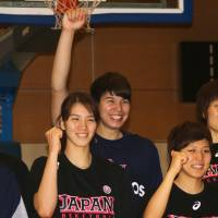 Ramu Tokashiki (center) poses for a photo along with her Japan teammates on Monday. With the return of Tokashiki from the United States, the 12-member  Japan women's national squad is ready to compete in the FIBA Asia Championship, which begins on Saturday in Wuhan, China. | KAZ NAGATSUKA