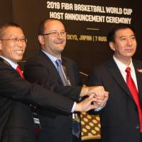 FIBA secretary general Patrick Baumann (center) and Chinese bid committee executives pose for a photo after the country won the host rights for the 2019 FIBA World Cup on Friday. | KAZ NAGATSUKA