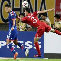 Japan's Tomoaki Makino (left) clears a North Korean attack during their East Asian Cup match in Wuhan, China, on Sunday. | KYODO