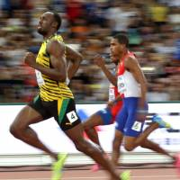Jamaica's Usain Bolt cruises to victory in a preliminary round heat of the men's 200 meters at the IAAF World Championships on Tuesday at the Bird's Nest in Beijing.   AP