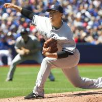 New York starting pitcher Masahiro Tanaka delivers during the second inning of the Yankees' 4-1 win over the Blue Jays on Saturday. | AP
