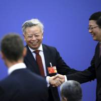 Jin Liqun (left) shakes hands with Chinese Finance Minister Lou Jiwei ahead of a signing ceremony for articles of agreement of the Asian Infrastructure Investment Bank at the Great Hall of the People in Beijing on June 29. | REUTERS