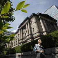 A pedestrian walks past the Bank of Japan headquarters in Tokyo. Some BOJ officials see a growing likelihood the central bank will lower its inflation outlook again. | BLOOMBERG