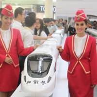 Indonesian models stand with scale models of Chinese-made bullet trains at a shopping mall in Jakarta in August. | KYODO