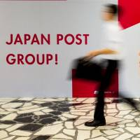 A pedestrian passes a poster at the Tokyo headquarters of Japan Post in June. Japan Post Holdings Co. and its banking and insurance units will begin trading on the Tokyo Stock Exchange on Nov. 4, the bourse announced Thursday. | REUTERS