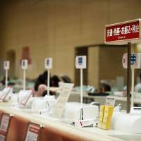 Teller stations stand at the flagship branch of Bank of Tokyo Mitsubishi UFJ in Tokyo. | BLOOMBERG