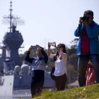 Chinese tourists stand in front of an Australian naval ship as they photograph the Sydney Opera House and harbour bridge on Monday. | REUTERS
