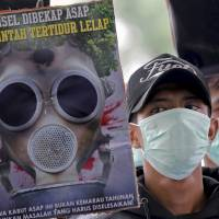 Protesters rally Tuesday outside the office of the governor of South Sumatra in Palembang, Indonesia, calling for the immediate end to forest fires in the province. | REUTERS