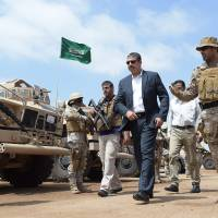Saudi forces stand to attention during a visit by Yemeni Prime Minister Khaled Bahah at the Saudi-led coalition military base in Yemen's southern embattled city of Aden on Monday.   AFP-JIJI