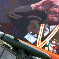 A veteran is shown saluting on a big screen as vehicles carrying missiles roll past in Beijing's Tiananmen Square on Thursday in a military parade marking the 70th anniversary of the end of World War II. | REUTERS