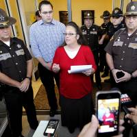 Freed Kentucky clerk back at work, lets deputies issue court-ordered same sex wedding licenses