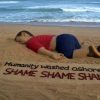 An artist works on a sand sculpture depicting drowned Syrian boy Aylan Kurdi at Puri beach, some 65 km from Bhubaneswar, India, on Friday. | AFP-JIJI
