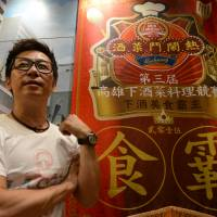 Ah Tong, a Hong Kong emigrant to Taiwan who runs a restaurant in Taipei, stands next to a banner showing his award in a Kaohsiung culinary competition. | AFP-JIJI