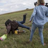 A migrant carrying a child falls after being tripped by a TV camerawoman while trying to escape from a collection point in Roszke village, Hungary, Tuesday. | REUTERS