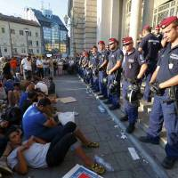 Refugees form a sit-down demonstration as police block the entrance to the main Eastern Railway station in BudapestTuesday. Hundreds of angry migrants demonstrated on Tuesday demanding they be allowed to travel on to Germany, as the biggest ever influx of migrants into the European Union left its asylum policies in tatters. Around 1,000 people waved tickets, clapping, booing and hissing, and shouting 'Germany! Germany!' outside the station. A refugee crisis rivalling the Balkan wars of the 1990s as Europe's worst since World War II has polarized and confounded the European Union, which has no mechanism to cope with the arrival of hundreds of thousands of poor and desperate people. | REUTERS