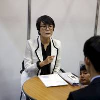 A consultant advises a job seeker at an employment fair in Seoul on Wednesday. | REUTERS