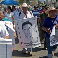 A relative of Mexican missing student Jhosivani Guerrero de la Cruz holds his portrait during a march in Acapulco, Guerrero State, Mexico, on March 4. Jhosivani Guerrero is the second of the 43 missing students of Ayotzinapa whose remains are identified, the Mexican government informed on Wednesday. Mexican authorities announced the arrest Thursday of a prime suspect in the massacre, but relatives doubt the truth will come out. | AFP-JIJI