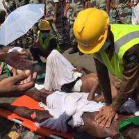 In this image, posted on the official Twitter account of the Saudi Civil Defense agency directorate, a pilgrim is treated by a medic after a deadly stampede in the holy city of Mina during the annual hajj pilgrimage on Thursday. | AP