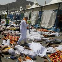 A muslim pilgrim walks through the site where dead bodies are gathered in Mina, Saudi Arabia, following a horrific stampede during the annual hajj pilgrimage on Thursday.. | AP