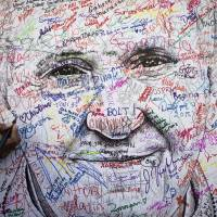 A pilgrim attending the World Meeting of Families signs a poster drawing of Pope Francis, by artist Mark Gaines, in Philadelphia on Wednesday. | REUTERS