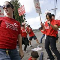 Teachers Sarah Martin (left) and Ina Shepard (with microphone) lead cheers during picketing in front of Chief Sealth International High School Wednesday in Seattle. Teachers in Seattle began walking picket lines Wednesday after last-minute negotiations over wages and other issues failed to avert a strike in Washington state's largest school district. | AP