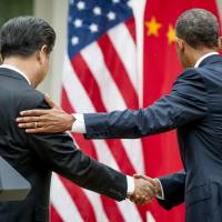 Chinese President Xi Jinping shakes hands with U.S. President Barack Obama as they leave a joint news conference in the Rose Garden of the White House in Washington on Friday. | BLOOMBERG