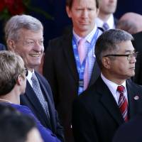 U.S. Ambassador to China Max Baucus (left) and former U.S. Ambassor to China Gary Locke wait with other dignitaries for the arrival of Chinese President Xi Jinping Tuesday at Boeing Field in Everett, Washington. | AP